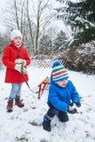 Дети играя в снеге в зиме Стоковые Изображения RF