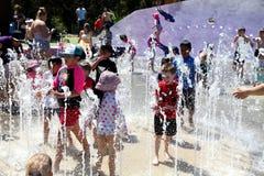 Дети играя в фонтане в горячем дне Стоковая Фотография