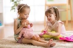 Дети играя доктора с куклой крытой стоковые фото