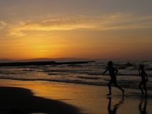 Дети играя заход солнца пляжа моря 2 мальчика бежать на пляже на времени захода солнца стоковое изображение rf