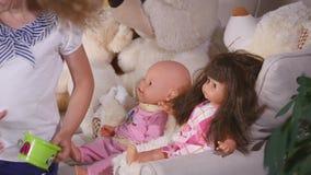 Дети играя игру как вызванная игра мат-дочери одна девушка подают кукла с пластичной ложкой сток-видео