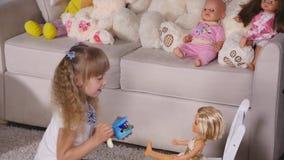 Дети играя игру как вызванная игра мат-дочери одна девушка подают кукла с пластичной ложкой акции видеоматериалы