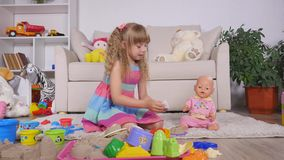 Дети играя игру как вызванная игра мат-дочери одна девушка подают кукла с пластичной ложкой видеоматериал