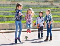 Дети играя игру прыгая веревочки скача Стоковая Фотография