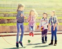 Дети играя игру прыгая веревочки скача Стоковые Изображения