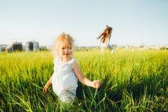 Дети играя наверстывание в зеленом поле на заходе солнца Стоковая Фотография