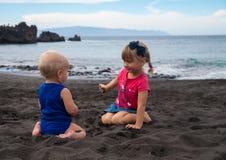 Дети играя на песке черноты арены Ла Playa вулканическом приставают к берегу Стоковое Изображение RF