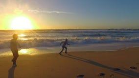 Дети играя на пляже, заход солнца в Half Moon Bay видеоматериал