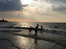 Дети играя на пляже на заходе солнца Стоковые Фотографии RF