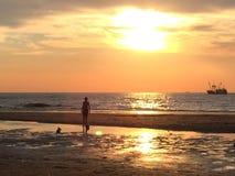 Дети играя на пляже на заходе солнца Стоковое Фото
