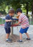 Дети играя на спортивной площадке Стоковые Изображения