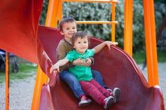 Дети, играя на спортивной площадке Стоковые Фото