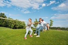 Дети играя перетягивание каната на зеленой траве в парке Стоковое Изображение