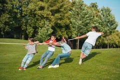 Дети играя перетягивание каната на зеленой траве в парке Стоковое фото RF