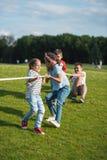 Дети играя перетягивание каната на зеленой траве в парке Стоковая Фотография