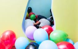 Дети играя с воздушными шарами во время playtime в интерьере ki Стоковая Фотография