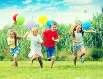 Дети играя с красочными воздушными шарами Стоковые Изображения RF