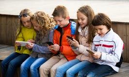 Дети играя с мобильными телефонами Стоковая Фотография RF