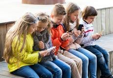 Дети играя с мобильными телефонами Стоковое Изображение