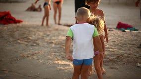 Дети играя с песком на пляже моря семейный отдых лета акции видеоматериалы