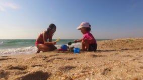 Дети играя с песком на пляже видеоматериал