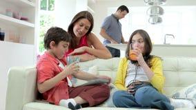 Дети играя с приборами цифров как родители делают еду сток-видео