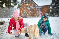 Дети играя с снегом и собакой стоковые фото
