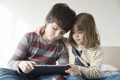 Дети играя с цифровой таблеткой стоковые фотографии rf