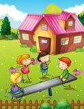 Дети играя с seesaw в задворк Стоковые Фото