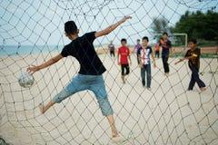 Дети играя футбол пляжа на Setiu, Terengganu, Малайзии