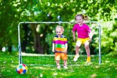 Дети играя футбол в школьном дворе Стоковая Фотография