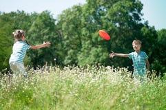 Дети играя frisbee стоковое изображение rf