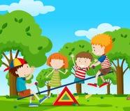 Дети играя seesaw в парке Стоковые Фото