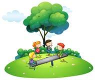 Дети играя seesaw в парке Стоковое Фото