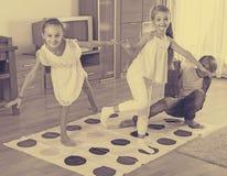 Дети играя twister дома Стоковое фото RF