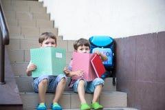 Дети идут назад к школе Старт нового учебного года после летних каникулов 2 друз с рюкзаком и книгами на первом schoo Стоковое Изображение RF