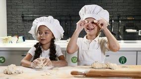 Дети имея потеху варя совместно при закрытых дверях кухню Концепция шеф-повара детей Тесто, мука и вращающая ось на таблице сток-видео