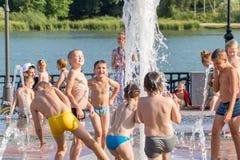 Дети имея потеху в фонтане на обваловке реки надевают в России Стоковое Изображение RF