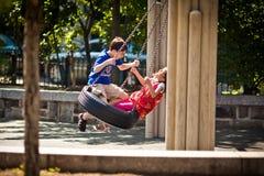 Дети имея потеху на качании, Нью-Йорк, США Стоковое Изображение RF