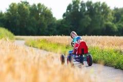 Дети имея потеху с автомобилем тележки идти Стоковые Фото
