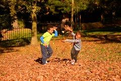 Дети имея потеху с листьями осени в парке
