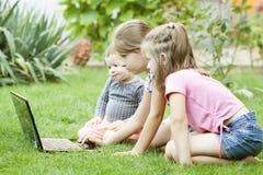 Дети используя компьтер-книжку в луге Стоковое фото RF