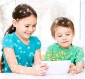 Дети используя планшет стоковое фото