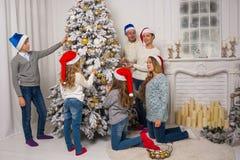 Дети и взрослые украшают рождественскую елку Стоковые Изображения
