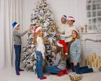 Дети и взрослые украшают рождественскую елку Стоковое Изображение