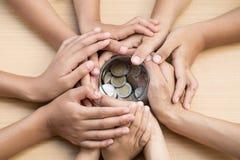 Дети и взрослый держа деньги раздражают, пожертвование, сохраняя концепцию стоковое фото rf