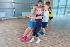 Дети и воссоздание, группа в составе счастливая многонациональная школа ягнятся играть перетягивание каната с веревочкой в спортз Стоковая Фотография