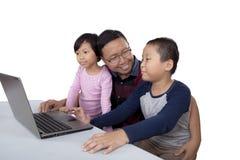 Дети и компьтер-книжка пользы папы на таблице Стоковая Фотография
