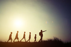 Дети и родитель силуэтов идя с рюкзаками Время к Стоковые Фото