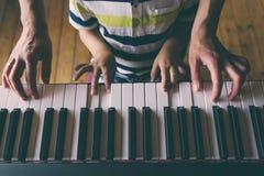 Дети и руки женщин на ключах рояля стоковая фотография rf
